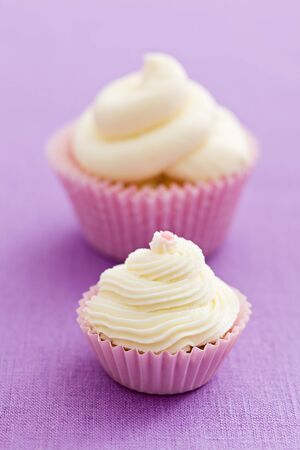 Two vanilla cupcakes with buttercream swirl topping on pink tablecloth