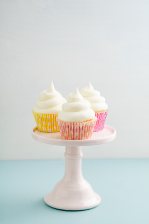 Three cupcakes with buttercream frosting on a cake stand