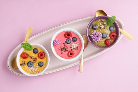 Three smoothie bowls with blueberries, raspberries, kiwi and peach