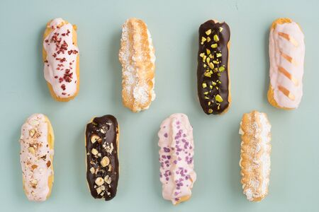 Eclairs with chocolate ganache and icing with different toppings Banco de Imagens