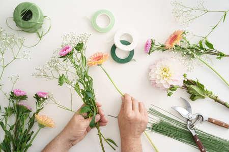 Man regelen bloemen aan een boeket te maken Stockfoto