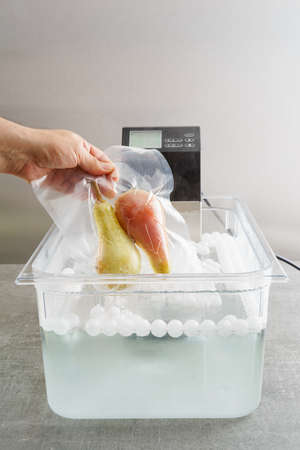 Sous vide cooking of pears in a sous vide precision immersion cooker with water and water balls Banco de Imagens