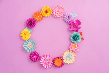 Kleurrijke kroon gemaakt van handgeschept papier bloemen op roze achtergrond Stockfoto