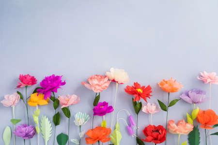 Kleurrijke handgeschept papier bloemen op lichtblauwe achtergrond met copyspace