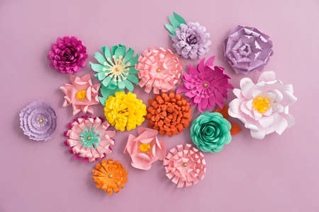 Colourful handmade paper flowers on pink background Standard-Bild