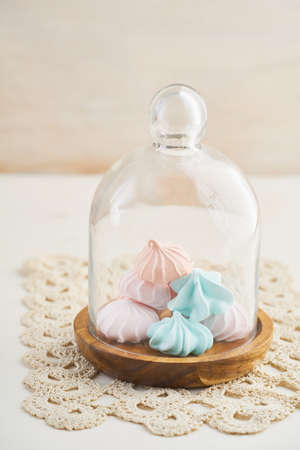 Patels colored meringue kisses on wooden glass dome display