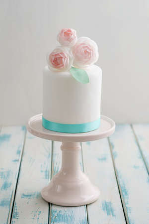Mini white fondant covered wedding cake with wafer paper ranunculus mini white fondant covered wedding cake with wafer paper ranunculus flowers on pink cake stand with mightylinksfo