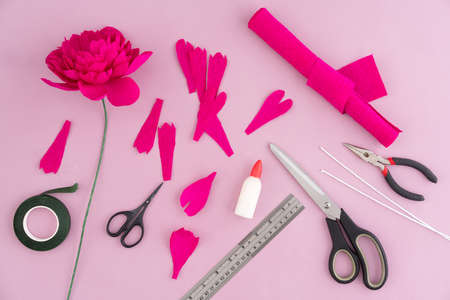 97306271 utensils and tools for making crepe paper flowers on pink wooden background