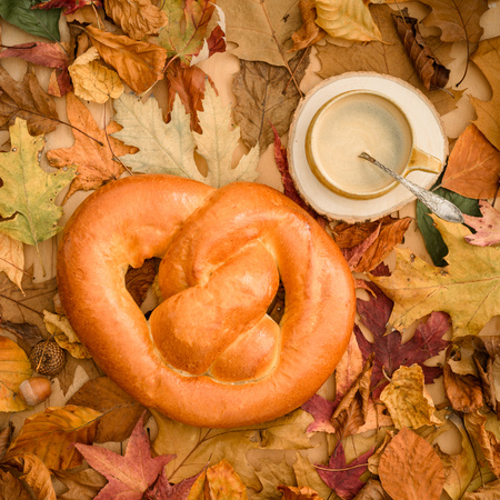 Sweet German white bread pretzel with a cup of coffee on autumn leaves