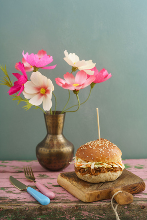 Pulled pork burger with homemade burger bun, pulled pork and coleslaw on rustic wooden board with paper flowers in a vase Stock Photo