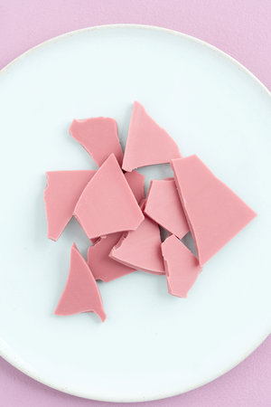 Broken pink Ruby chocolate bar pieces made from ruby cocoa beans on a turquoise plate
