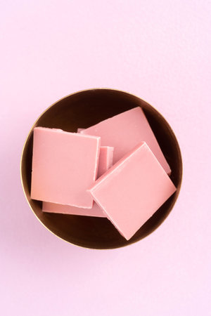 Broken pink Ruby chocolate bar pieces made from ruby cocoa beans in a bowl