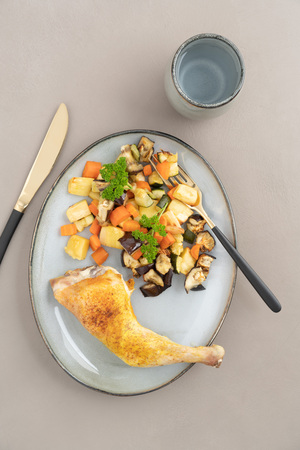 Place setting chicken dinner with oven roasted chicken leg and roasted vegetables Banco de Imagens