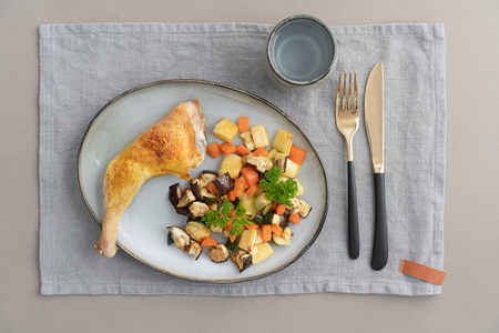 Place setting chicken dinner with oven roasted chicken leg and roasted vegetables Zdjęcie Seryjne
