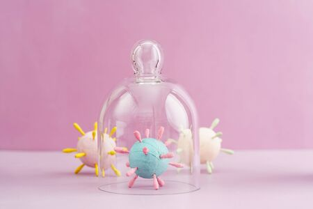 Hand crafted models of corona virus covid 19 against pink background, one virus is isolated