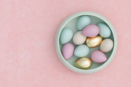 Colorful Easter eggs in a bowl on pink