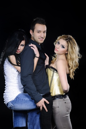 three persons: fashion three friends posing on black background Stock Photo