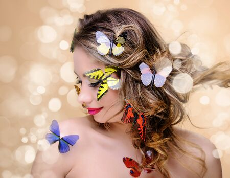 beautiful fashion woman with professional make-up surrounded by butterflyies photo