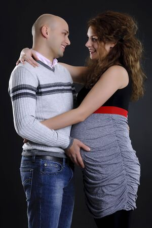 happy young family expecting a baby and posing on black background photo