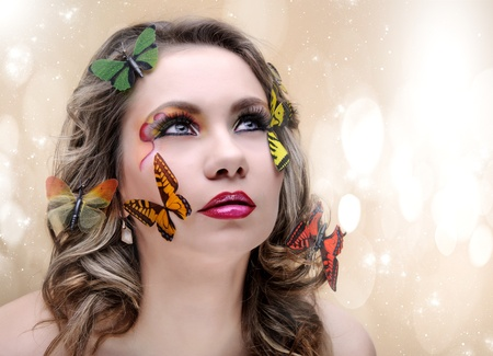 fashion beauty woman with eye make-up and butterfly photo