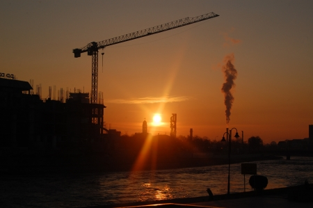 energy picture: crane and factory smoke with sunrise on the back Stock Photo