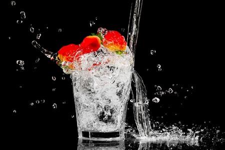 Splash in een glas met drie rode bessen en ijs op een zwarte achtergrond