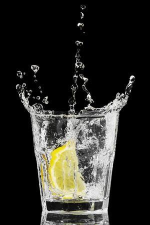 Splash in ein Glas mit Zitrone und Eis auf einem schwarzen Hintergrund