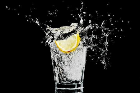 sports bar: splash in a glass with lemon and ice on a black background