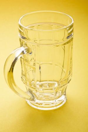 empty beer mug on a yellow background photo