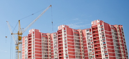 monolithic: The elevating crane against the dark blue sky, building a monolithic building. Stock Photo