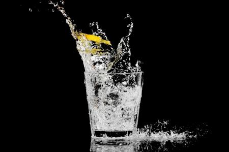 Splash in einem Glas mit Zitrone und Eis auf schwarzem Hintergrund Standard-Bild