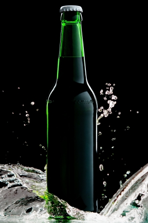 Beer in green bottle with water splash isolated on black Stock Photo