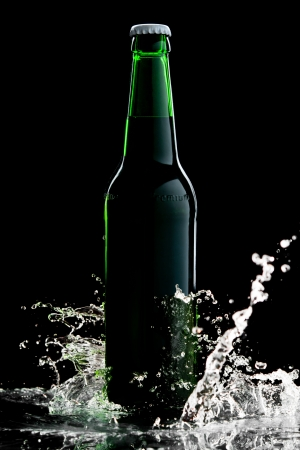Beer in green bottle with water splash isolated on black photo