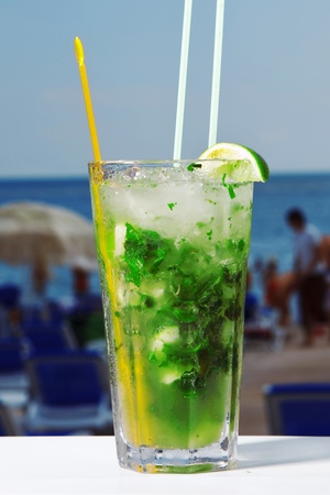 A glass of mojito cocktail with mint on beach and sky background photo