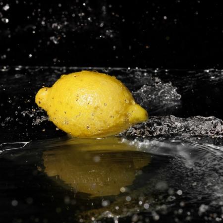 frisches Wasser Tropfen auf Zitrone auf schwarzem Hintergrund Standard-Bild