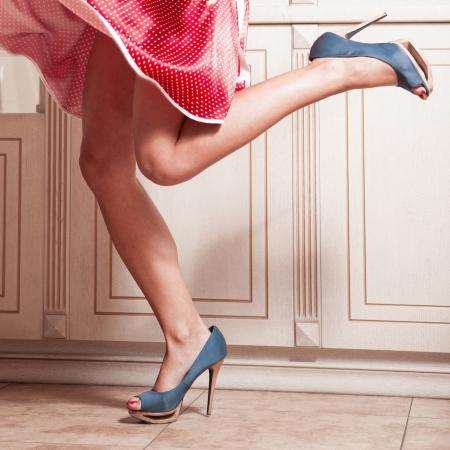 Schöne Frau Beine in roten Kleid mit blauen Schuhen mit hohen Absätzen