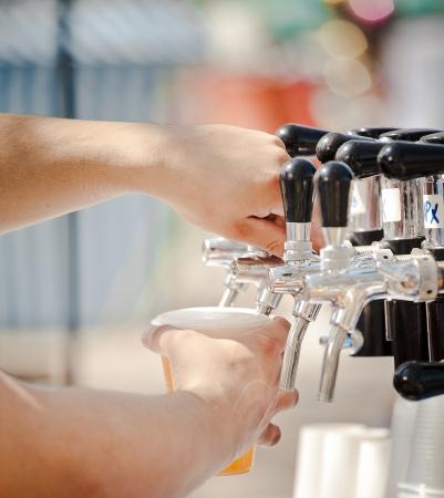 Bier tappen om plastic glazen van bier tap