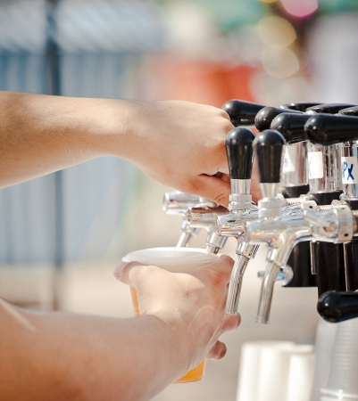 Pouring beer to plastic glass from beer tap Standard-Bild
