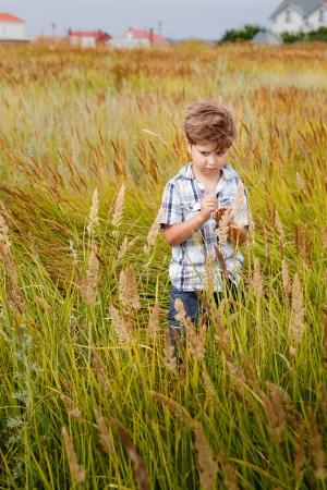 beatitude: Joyful little boy running around in a field