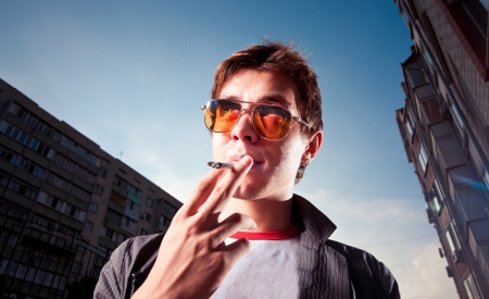 cigar: Young man smoking a cigarette on a city street