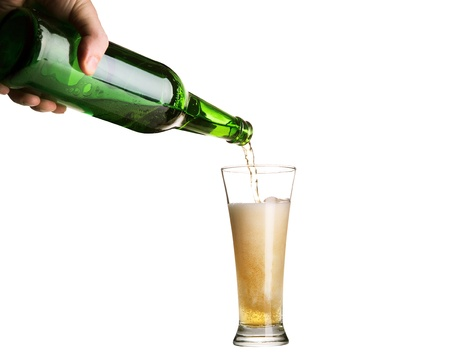 Beer pouring from green bottle into glass isolated on white photo