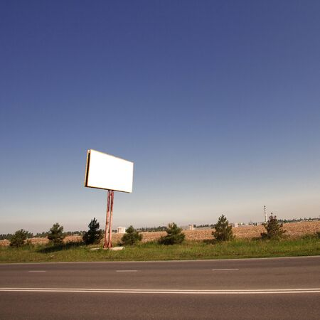 Road in a village with an empty billboard photo