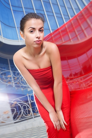 Young beautiful girl with the red flying fabric in the city photo