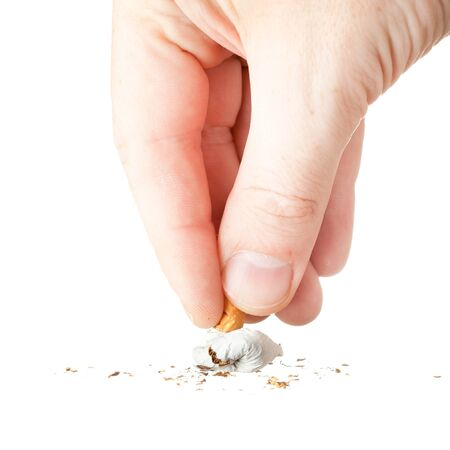 a hand extinguishing a cigarette on white background photo