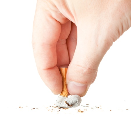 a hand extinguishing a cigarette on white background Stock Photo - 16246942