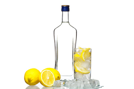 tipple: Bottle of vodka and wine glass with lemon and ice isolated on white