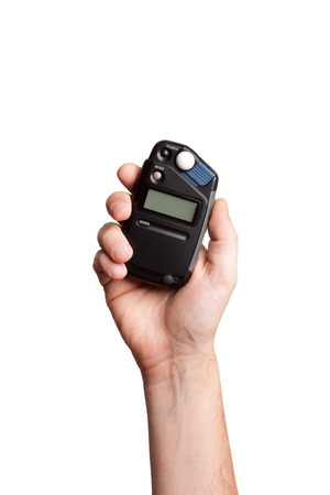 flash meter in hand on white background photo