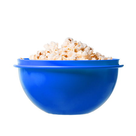 Salted popcorn grains in blue dish on white background photo