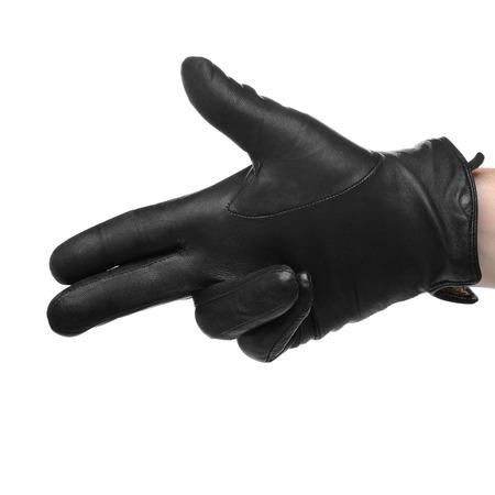 comunicacion no verbal: Una mano humana en el guante de cuero negro haciendo un tiroteo un gesto, aislado en fondo blanco Foto de archivo