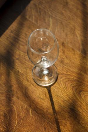 die ein leeres Weinglas auf einem Holztisch Standard-Bild
